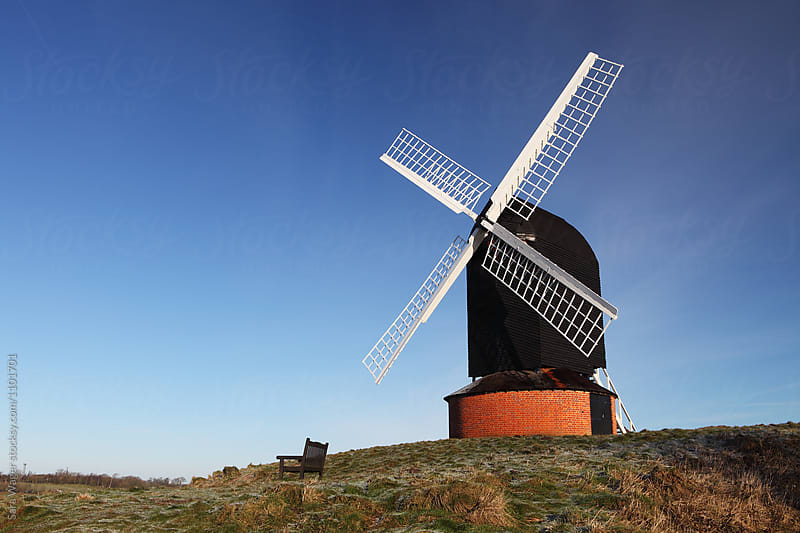 A windmill and solitary bench in the morning sun by Sara Wager for Stocksy United