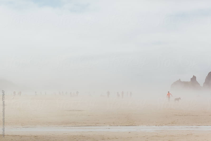 People on the beach in a foggy morning by michela ravasio for Stocksy United
