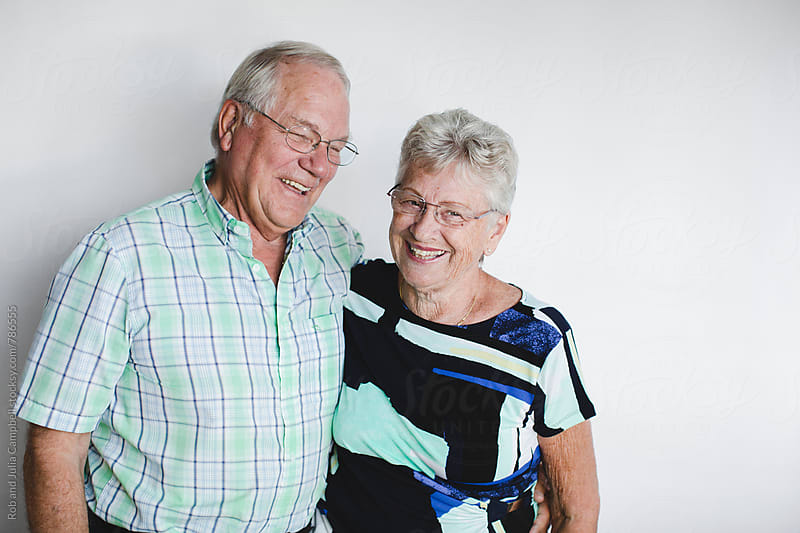 Senior couple enjoying each other in front of white background by Rob and Julia Campbell for Stocksy United