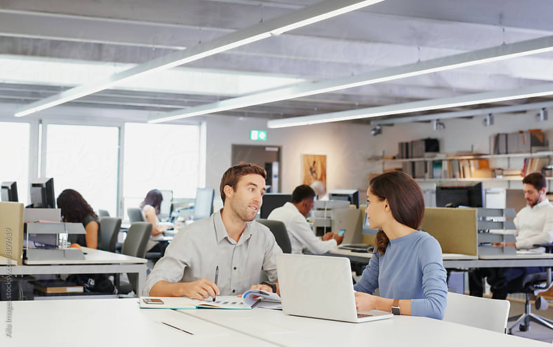 Business colleagues meeting at open plan board room table by Aila Images for Stocksy United