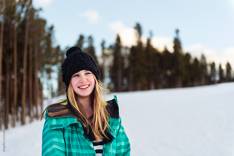 Smiling teenage girl outside in winter by Angela Lumsden for Stocksy United