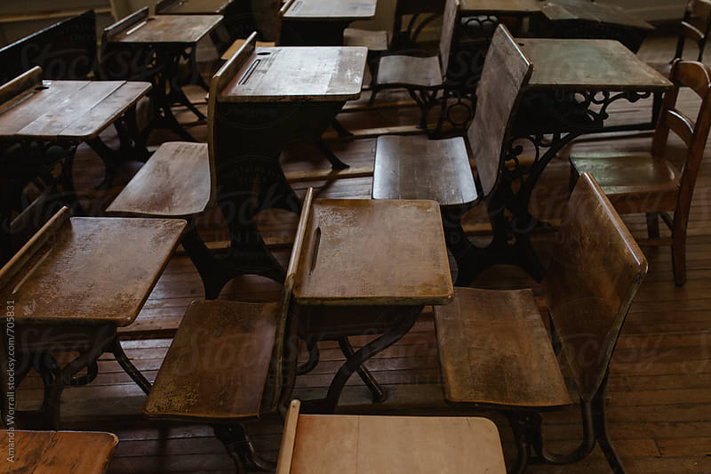 Rows of vintage school desks  by Amanda Worrall for Stocksy United