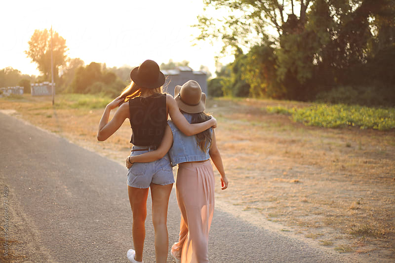 Two female friends walking down the road during the sunset.  by Marija Mandic for Stocksy United
