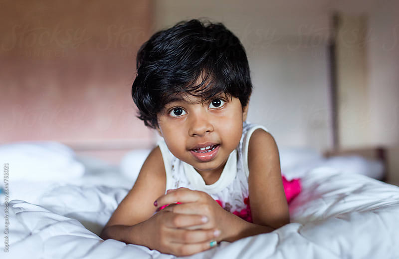 Smiling little girl lying on bed and looking at camera by Saptak Ganguly for Stocksy United
