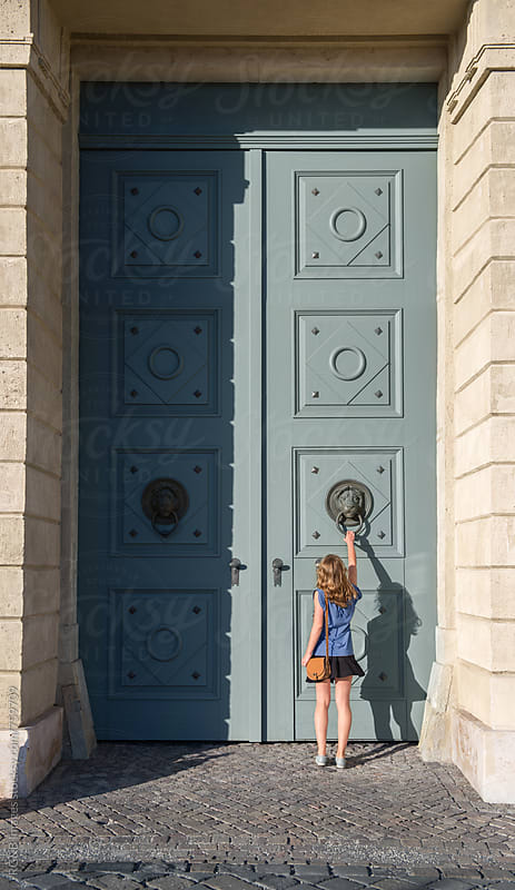 Young woman knocking at a huge door by RG&B Images for Stocksy United