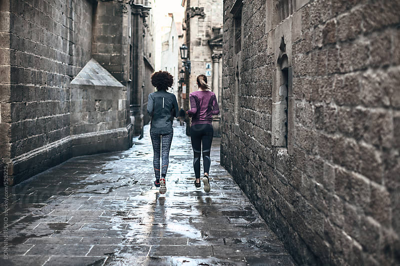 Back view of two young women running on Barcelona streets.  by BONNINSTUDIO for Stocksy United
