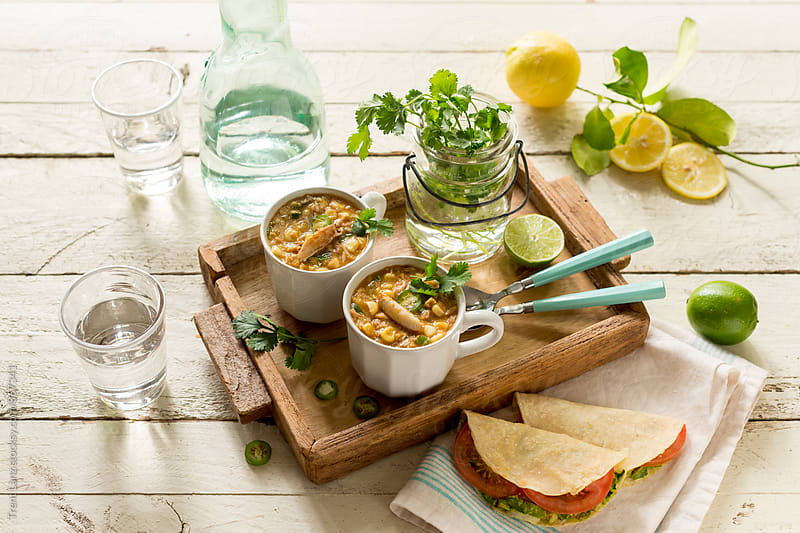 Delicious corn and crab summer chowder for two people on wooden tray. by Trent Lanz for Stocksy United