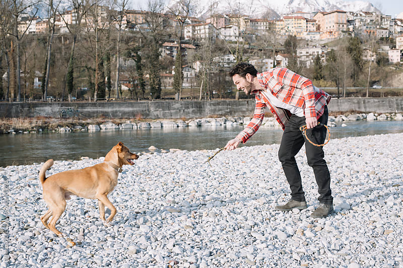 Man playing with dog near the river by Alberto Bogo for Stocksy United