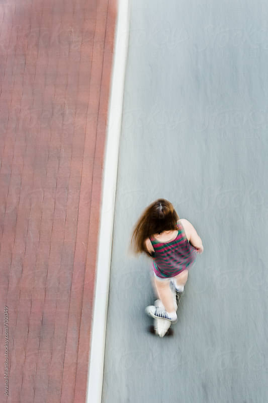 Above view of a girl on a longboard in the city by Jovana Milanko for Stocksy United