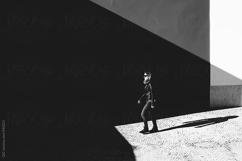 Woman walking in city shade by Simone Becchetti for Stocksy United
