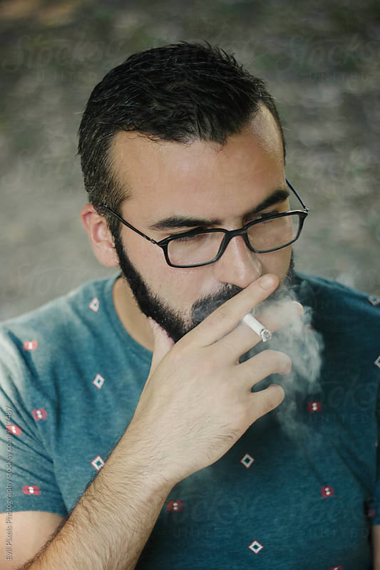 Portrait of a handsome male model with cigarette by Branislava Živić for Stocksy United
