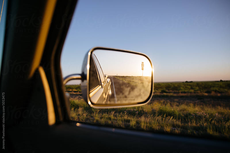 Sunset in side mirror of pickup truck on road trip by Jeremy Pawlowski for Stocksy United