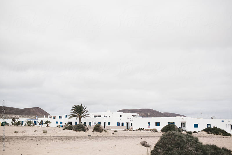 flat white homes on island on cloudy day by Nicole Mason for Stocksy United