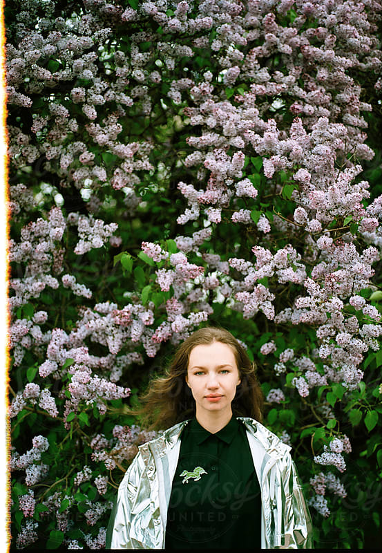 Portrait of young woman among lilac in blossom by Lyuba Burakova for Stocksy United