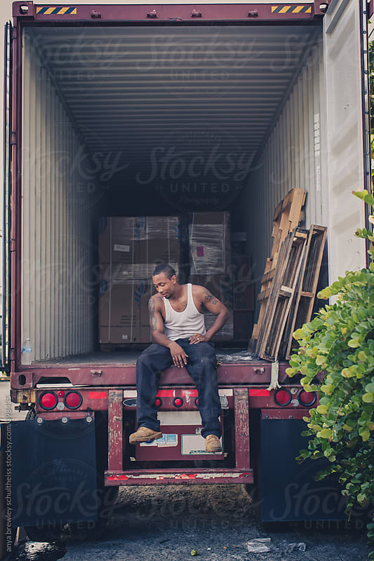 Portrait of a man sitting in an empty container and taking a break by anya brewley schultheiss for Stocksy United