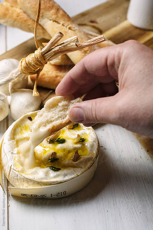 Hand dipping a chunk of crusty bread into a whole baked Camembert cheese. by Darren Muir for Stocksy United