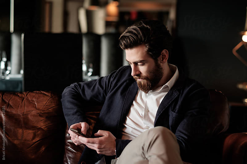 Handsome Bearded Man Using Phone by Branislav Jovanović for Stocksy United