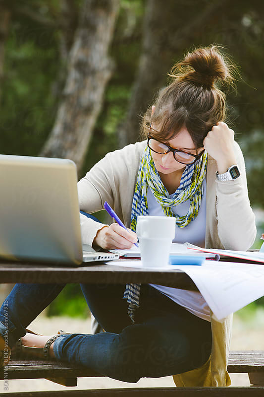 Beautiful young student with glasses with notes and laptop writing on a park. by BONNINSTUDIO for Stocksy United