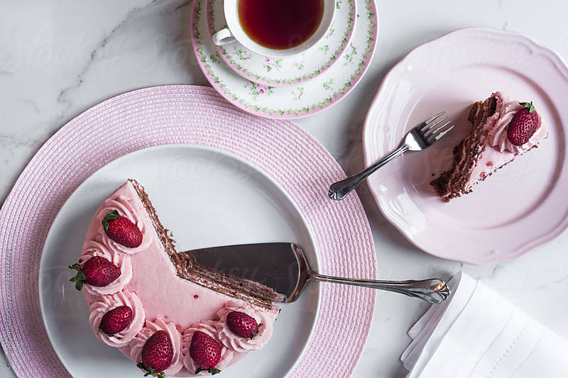 strawberry pink sponge cake with a cup of tea, on a marble background by Gillian Vann for Stocksy United