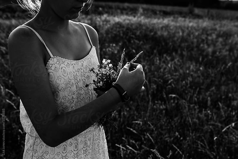 young woman picking wild flowers by Léa Jones for Stocksy United