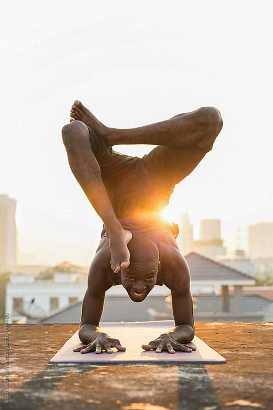 Handsome young man in a scorpion yoga pose on a rooftop at sunset  by Jovo Jovanovic for Stocksy United