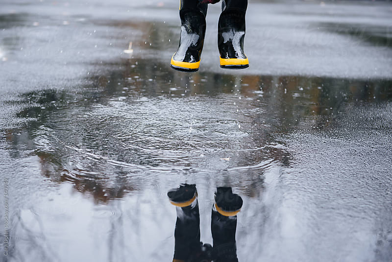 Child wearing rubber boots splashes in puddles on a rainy day by Cara Dolan for Stocksy United