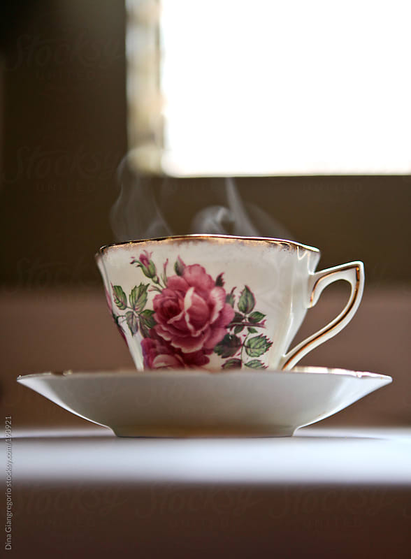 Delicate flowered tea cup near window with steam coming out by Dina Giangregorio for Stocksy United
