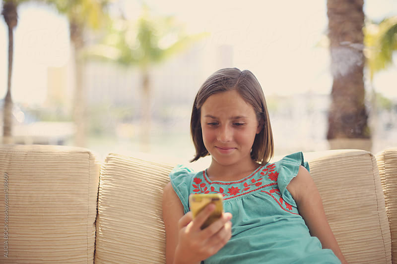 Tween Girl Playing On Her Phone While On Vacation by ALICIA BOCK for Stocksy United