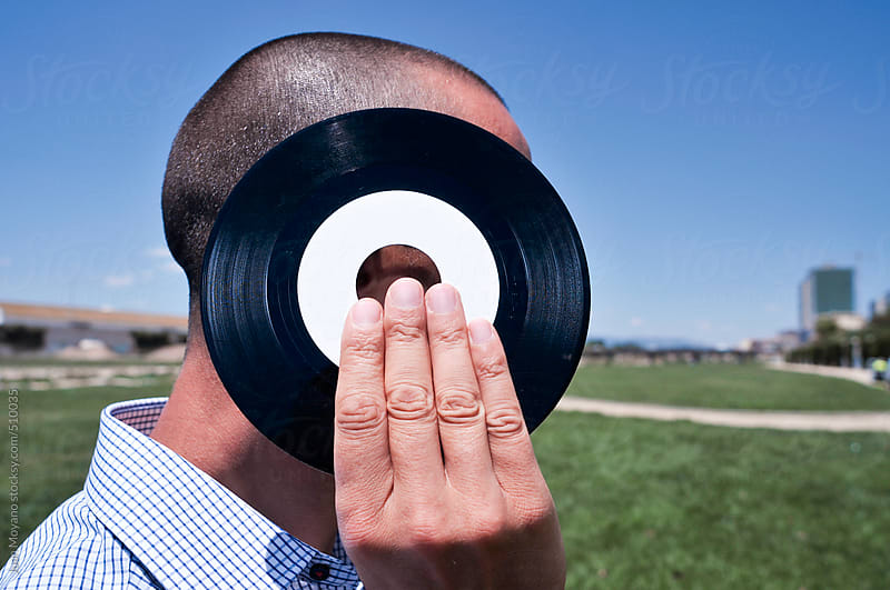 young man with a 45 rpm record at the park by juan moyano for Stocksy United