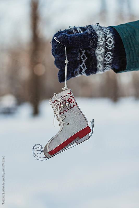 Hand holding skates by Tatjana Zlatkovic for Stocksy United