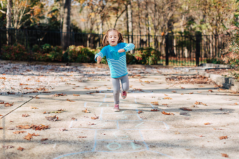 Cute young girl in pigtails doing hopscotch on a driveway by Jakob for Stocksy United