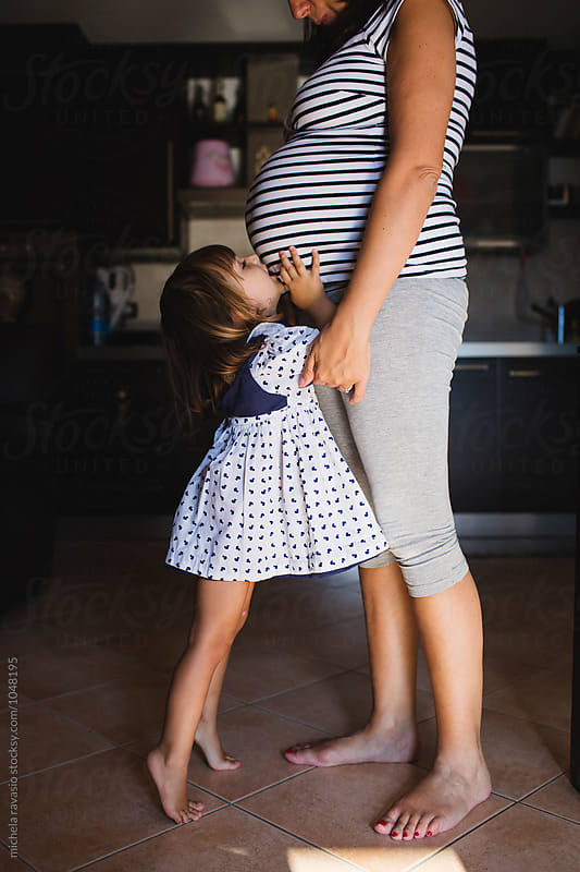 Little girl hugs her mom's belly by michela ravasio for Stocksy United