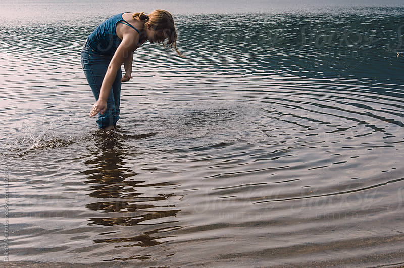 young teen girl splashing water water in a lake by Deirdre Malfatto for Stocksy United