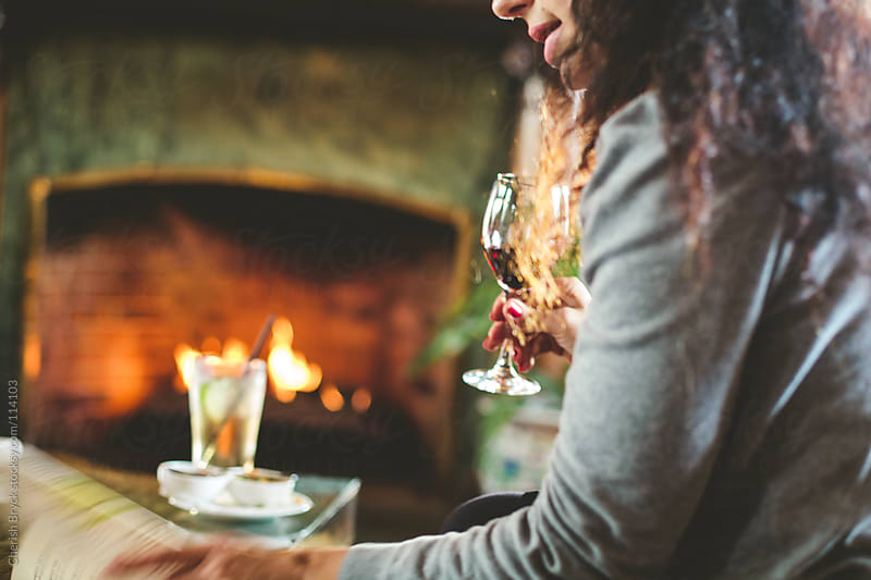 A woman sips wine by the fireplace. by Cherish Bryck for Stocksy United