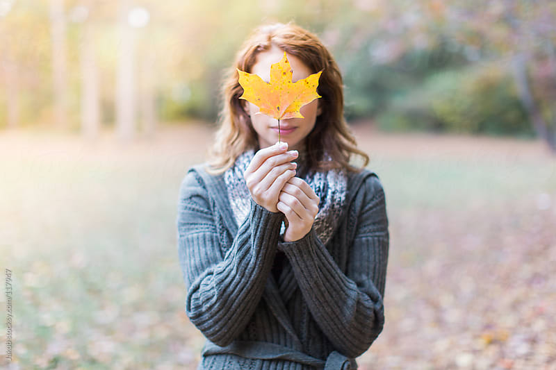 A woman holding a leaf in front of her face by Jakob for Stocksy United