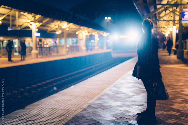 Girl stands waiting at an outdoor train station at night by Angela Lumsden for Stocksy United