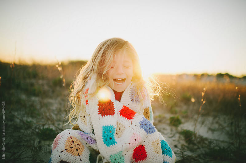 girl laughing in sunshine on beach  by Michelle Gardella for Stocksy United