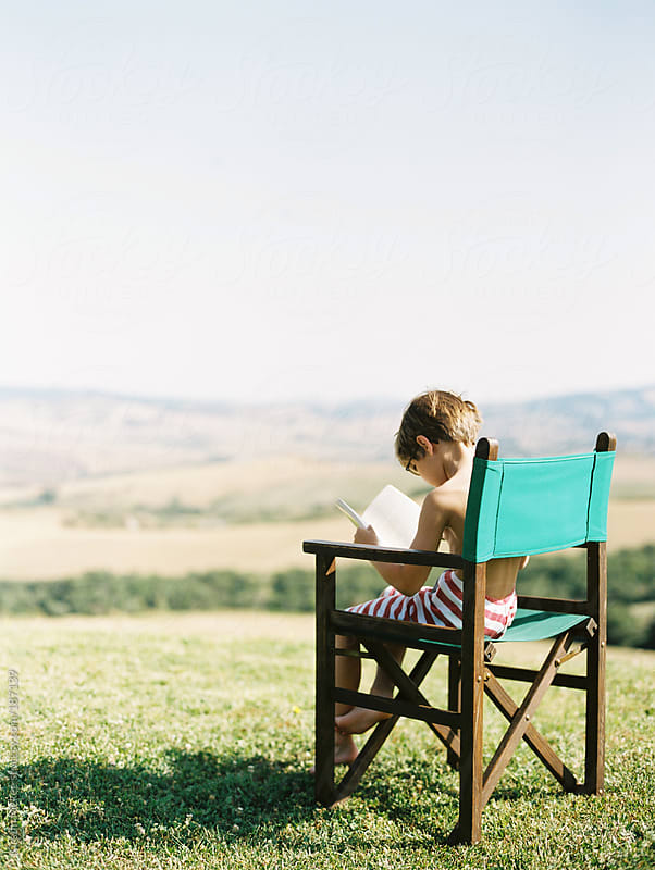 Boy reading book in Italian countryside by Kirstin Mckee for Stocksy United