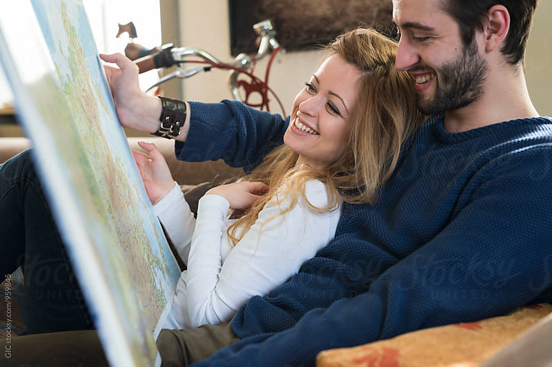 Young couple watching maps for holidays together at home by GIC for Stocksy United