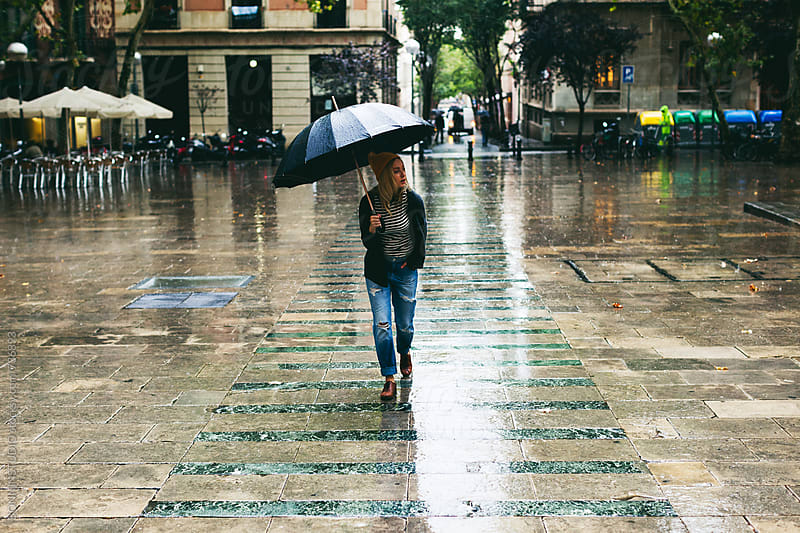 Woman walking on the street in a rainy day.  by BONNINSTUDIO for Stocksy United