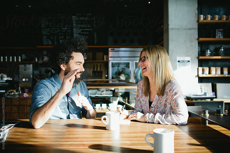 Man and woman laughing while having a conversation over coffee in a cafe by Kristine Weilert for Stocksy United