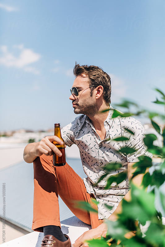 Portrait of a Young Handsome Man with a Beer Bottle by Victor Torres for Stocksy United