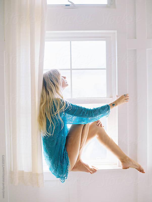 blonde girl in blue dress sitting in window by wendy laurel for Stocksy United