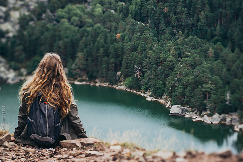 woman looks at the mountains and the lake by Javier Pardina for Stocksy United
