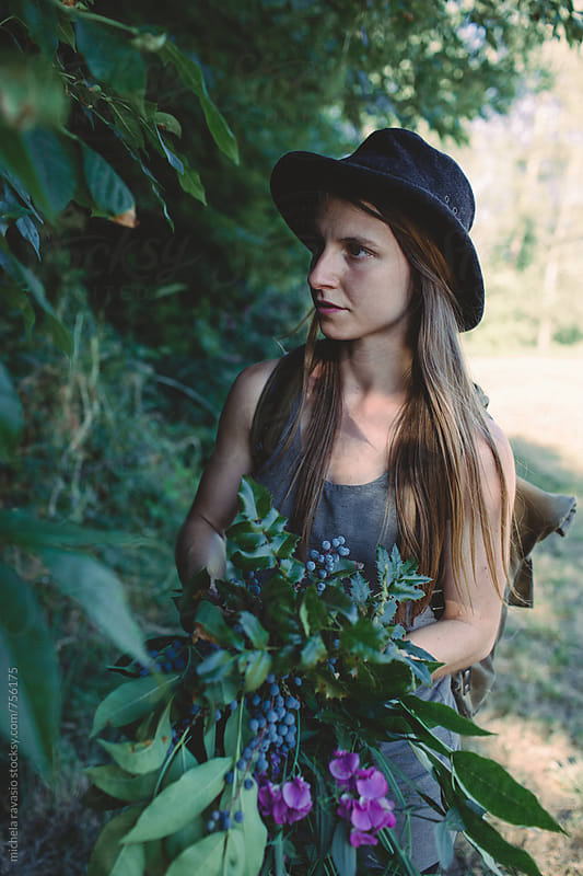 Young woman picking flowers and plants for floral composition by michela ravasio for Stocksy United