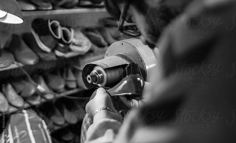 Shoemaker grinding shoe sole on grinder machine. by Marko Milanovic for Stocksy United