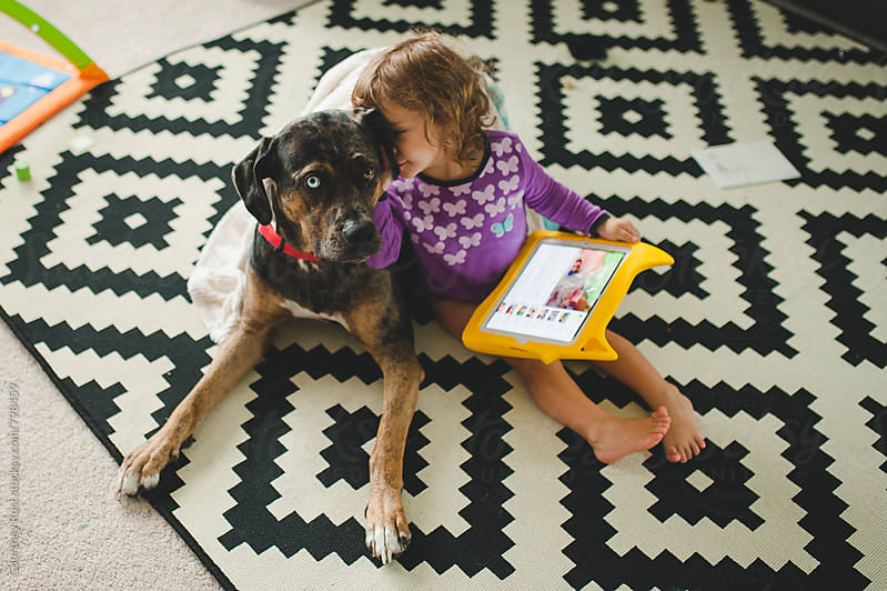 doggie snuggles with iPad time by Courtney Rust for Stocksy United
