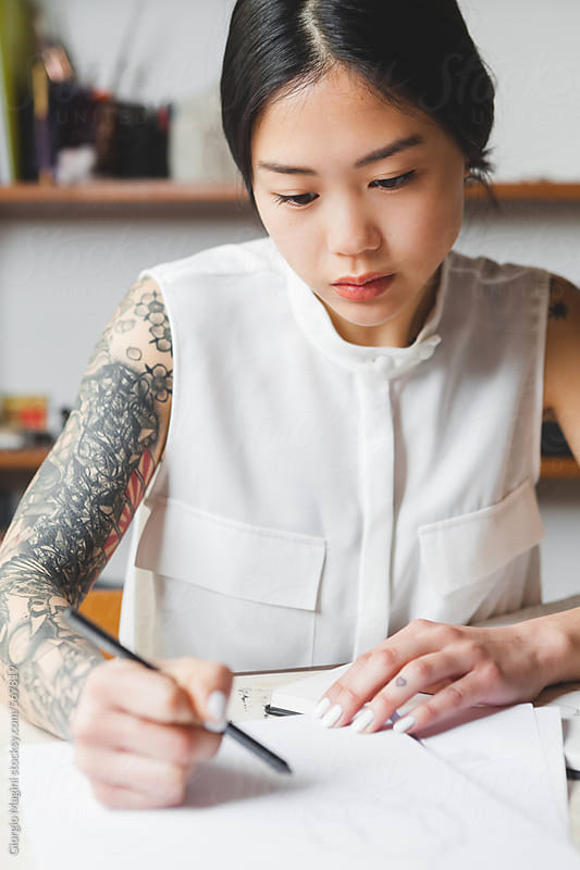 Portrait of a tattooed fashion designer drawing a sketch Japanese clothing designers