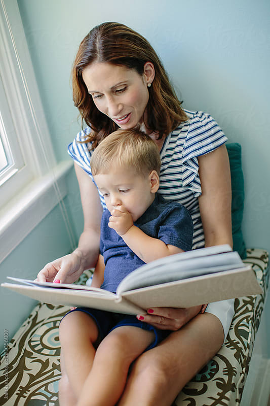 Mother sitting on a window sill reading a book to her son by Jakob for Stocksy United