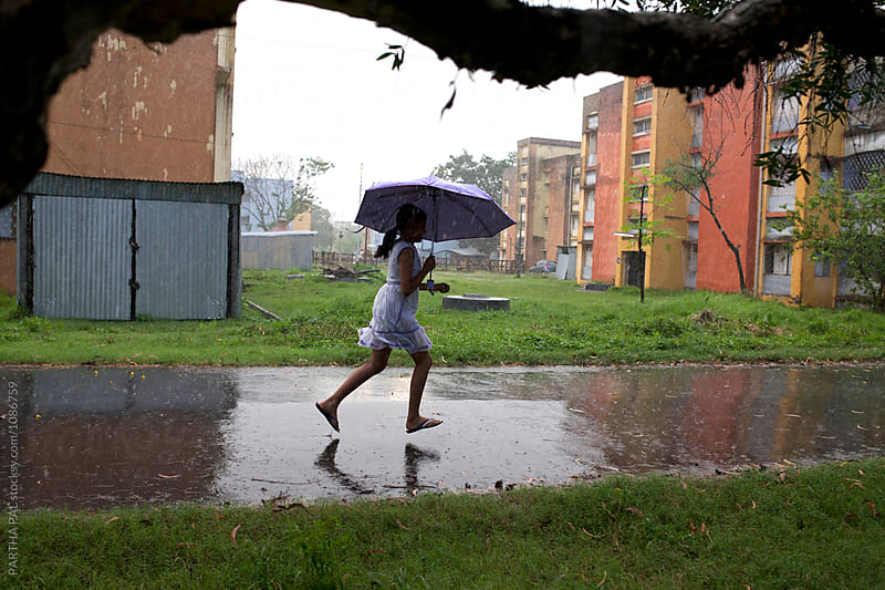 Teenage girl running in rain with blue umbrella by PARTHA PAL for Stocksy United